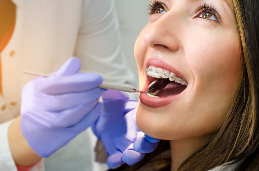Woman with braces being examined by an orthodontist at Robinson Orthodontics in Grants Pass, OR